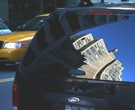Picture of Midtown NYC buildings reflected on an SUV