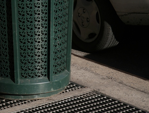 Hubcab, tire, rrash can and subway grate harmonize a pattern